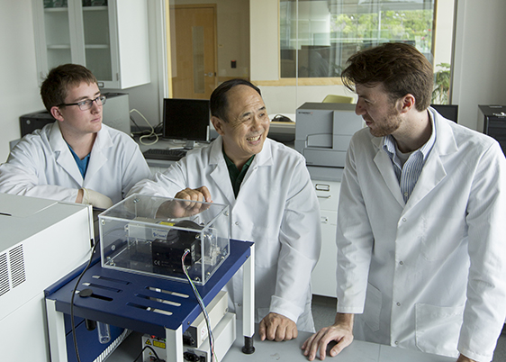Dr. Yinfa Ma in lab with Casey Burton and Alex Cristea , working on cancer detection technology
