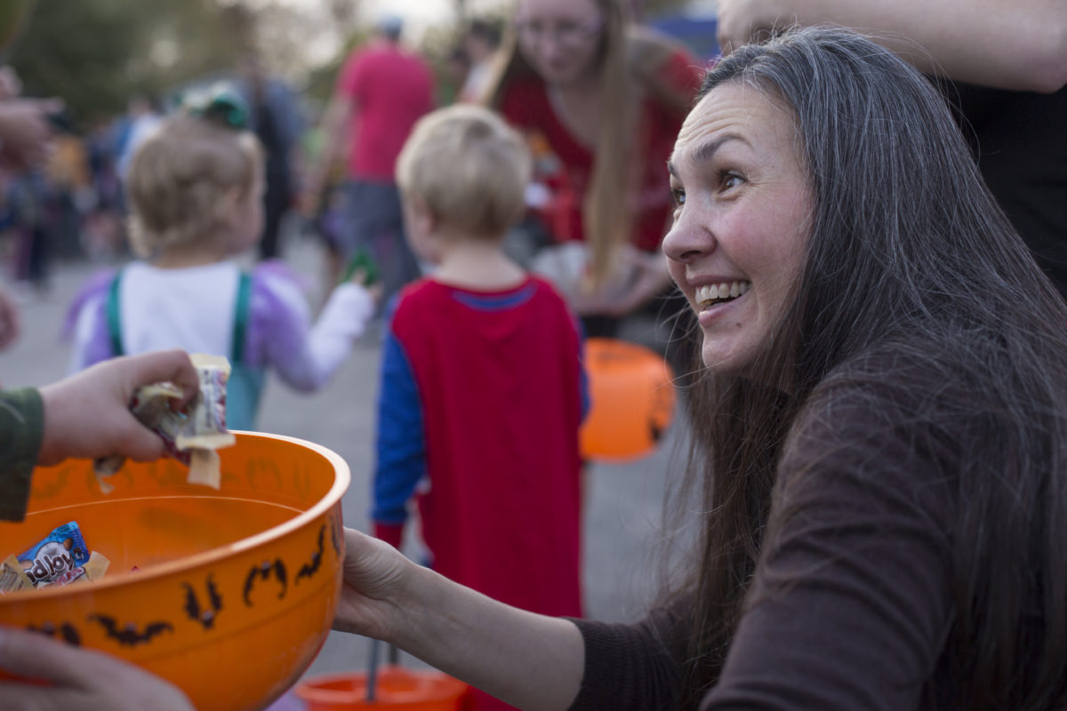 A woman holds out candy bowl to trick-or-treater.