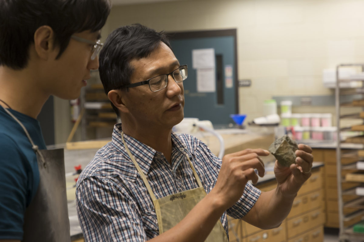 Dr. Wan Yang shows research student Ziyue Ju how to properly label and cut rock samples for analysis.