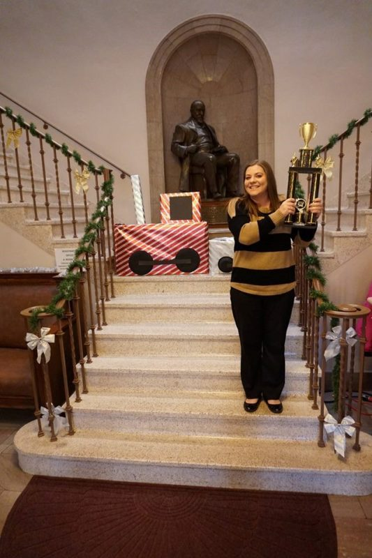 Brianna Land with traveling trophy and decorated collection container