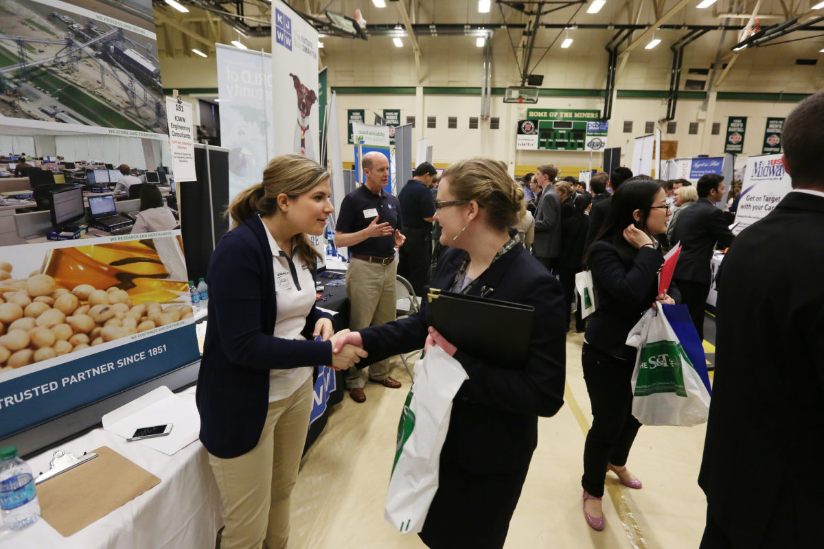 Student in business suit shaking hands with recruiter at career fair