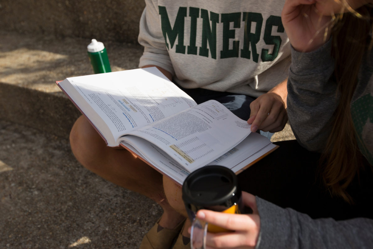 Two S&T students with a textbook.