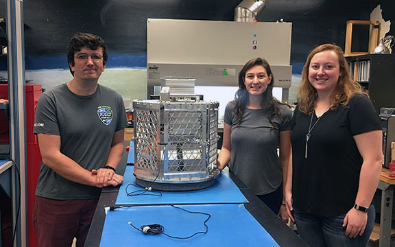 From left, graduate students Pavel Galchenko, Jill Davis and Donna Jennings pose with a satellite they are working on with grant funding.
