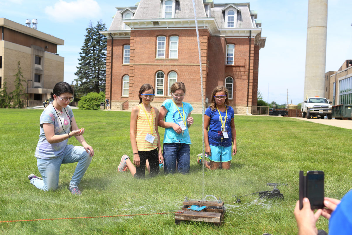 Four students launch a water rocket during aerospace camp.