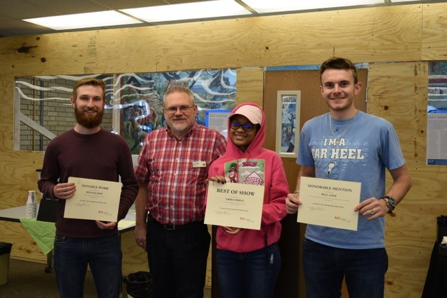 Student art award winners pose with Roger Weaver, chair of the Art in the Library Committee and scholarly librarian. From left, Ben Palmer, Roger Weaver, Erika Simple and Will Loos