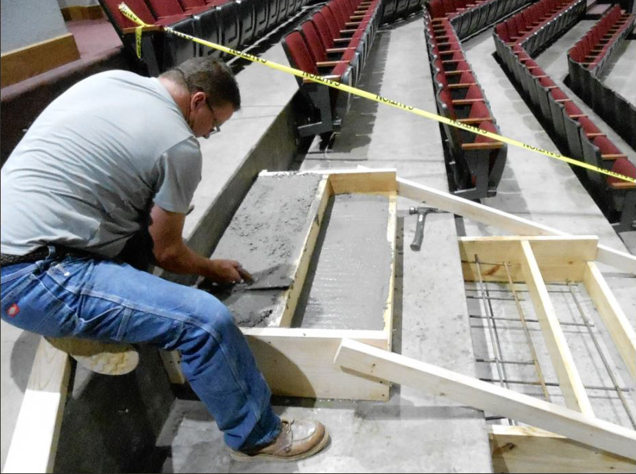 Workman shapes concrete stairs in center aisle.