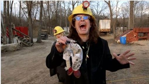 Ozzy Osbourne holds remains of doll that he blew up at S&T mine.
