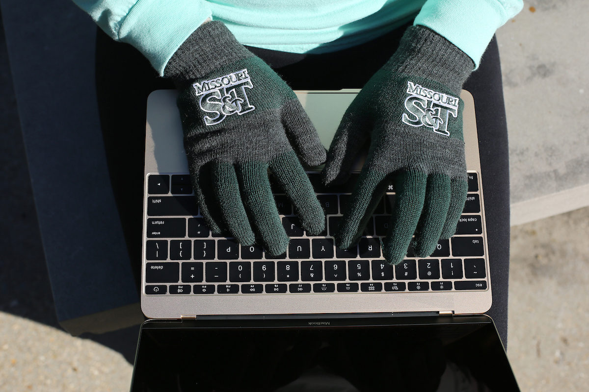 Student wearing S&T gloves on laptop
