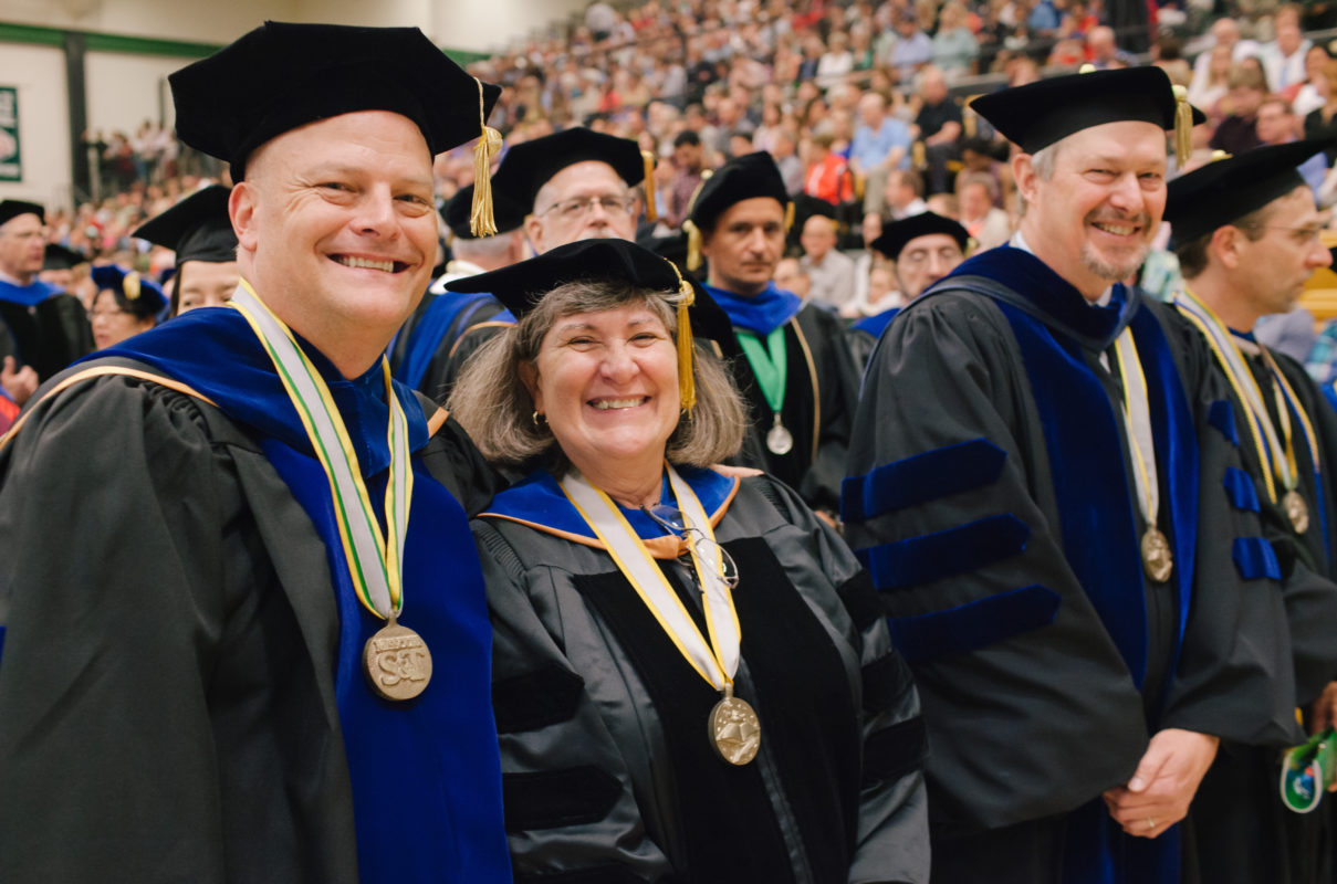 Faculty members standing at commencement