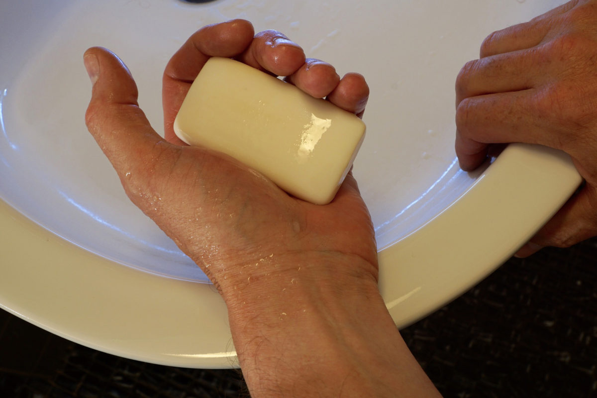 hand holding soap at sink