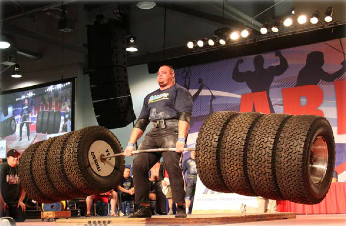 Man lifting tires in competition