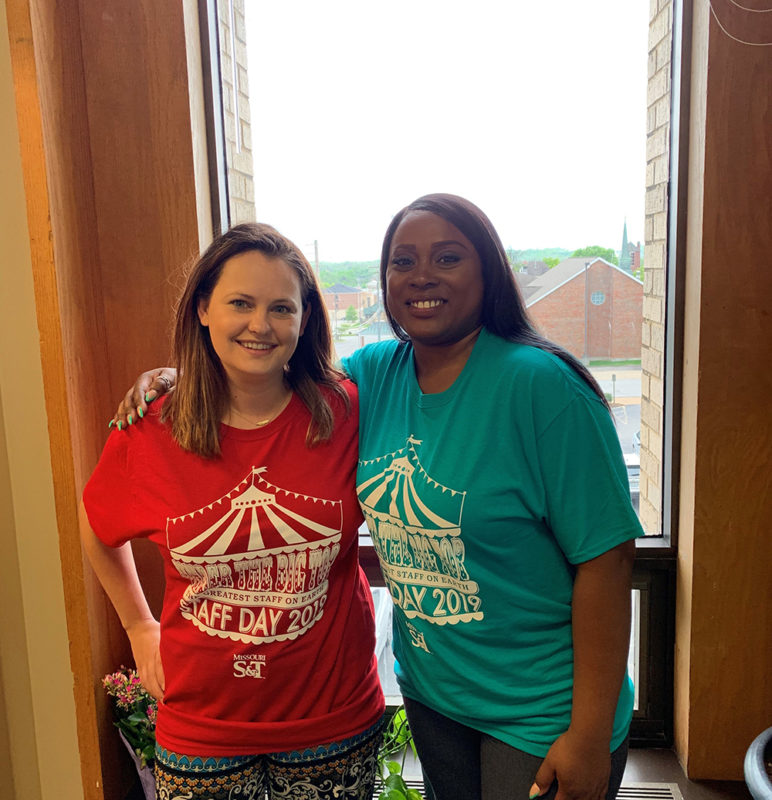 Two employees wearing Staff Day shirts